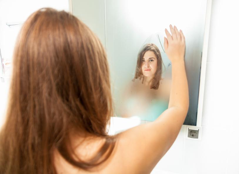 frau wischt beschlagenen spiegel ab