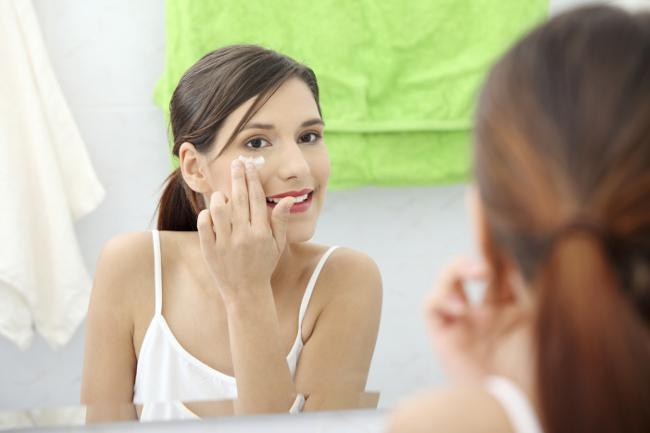 Frau, die sich vo dem Spiegel das Gesicht eincremt