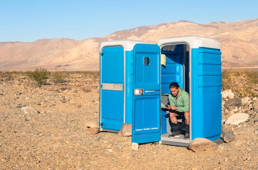Mann auf Klohäuschen mitten im Death Valley
