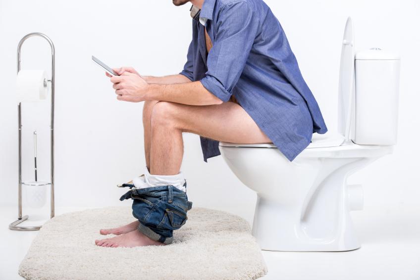 Mann sitzt mit Smartphone auf der Toilette