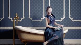 Frau in Kleid auf Badewanne vor klassischer blauer Tapete