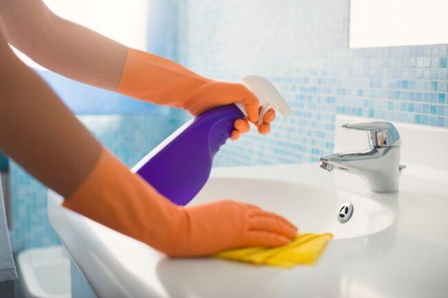 Frau reinigt Waschbecken